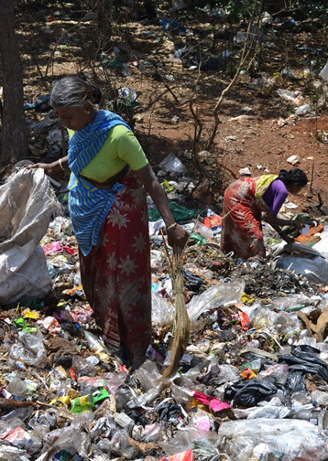 Waste pickers sort trash to find recyclable in landfill
