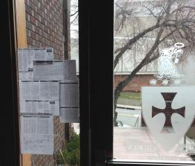 Public transit schedules hang on the door of the Sigma Chi fraternity.