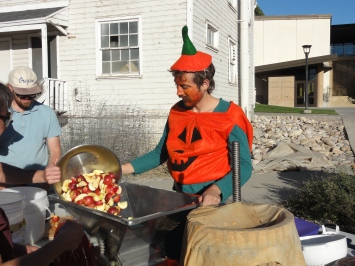 Becostumed volunteers press apples Friday at the fourth annual Edible Campus Gardens Fall Soiree and Service Project.