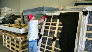 A Spring Back Utah employee disassembles a mattress inside the company's warehouse.
