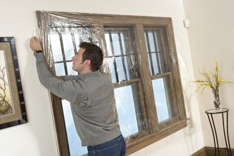 Install plastic over windows to create an additional barrier for heat loss. Photo by 3M.