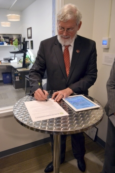 President David Pershing signs the Real Food Campus Commitment, making the U the largest school to commit to 20 percent real food by 2020, at the Sustainability Showcase and Open House on Feb. 9, 2015.