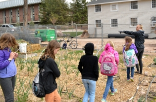 Garden steward Georgie Corkery leads 8 year olds on a tour through the Pioneer Garden.