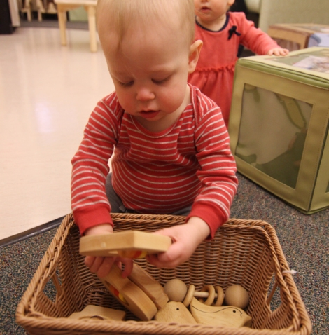 A baby plays with wooden toys, which are free from harmful lacquers.