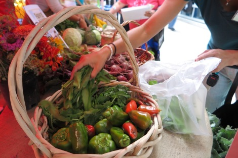 Person grabbing sorrel greens from a basket displayed on the Edible Campus Garden Farmers Market booth
