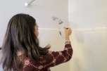 Isabelle Fernandez, an Energy Ambassador, tests water flow from a shower. The team will replace shower heads with a high efficiency, 1.5 gallon per minute shower head provided by Questar. Even better? It is free!