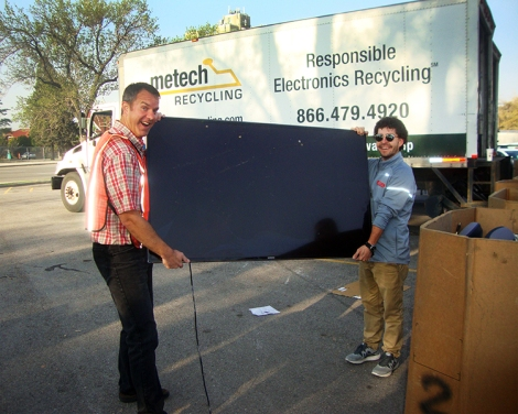 Volunteers from Staff Council move a large TV toward the Metech Recycling truck.