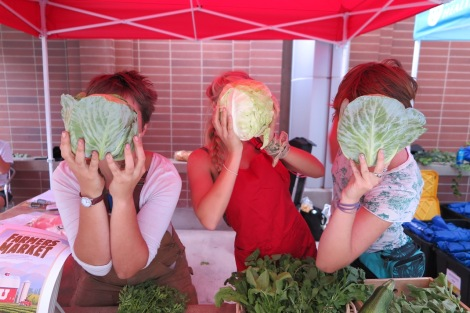 Edible campus garden staff show off our cabbage crop at the Farmers Market.