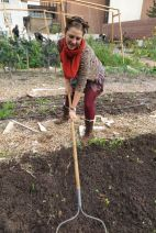 Garden steward Erika Longino, prepares the planting beds with fresh compost soil.
