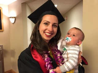 Liz Ivkovich, wearing her cap in gown, is holding her baby.