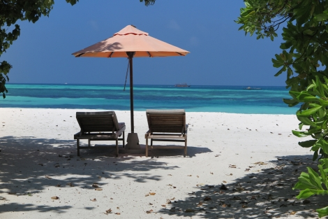 white beach with two lounge chairs and an umbrella