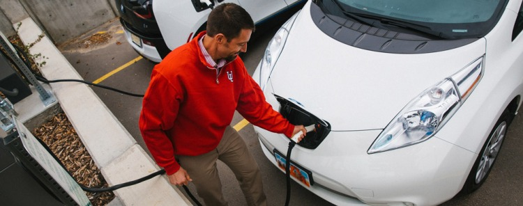 Man in University of Utah fleece charges his electric vehicle.