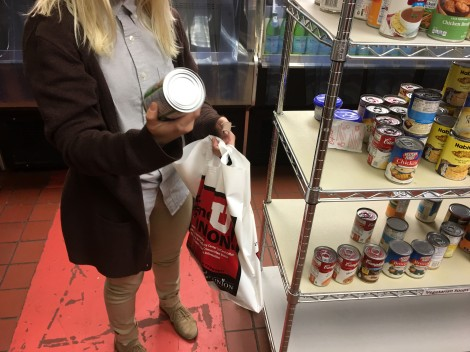 Student looks at the label of a canned good in the food pantry.